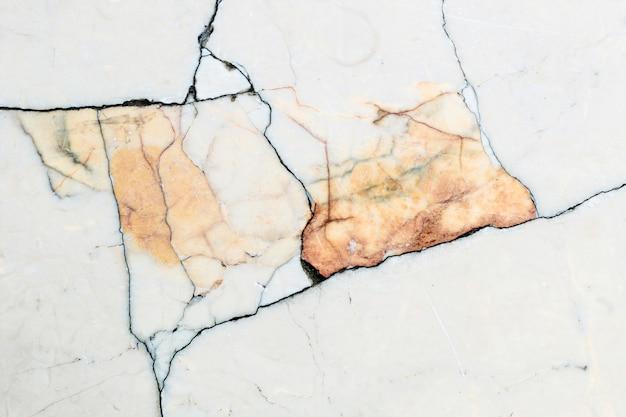 Gładka marmurowa faktura ścian z ciemnymi paskami i żółtymi wstawkami z kamienia.