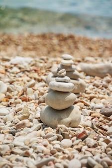 Gładkie kamienie ułożone na sobie na plaży. wieża kamieni do medytacji.