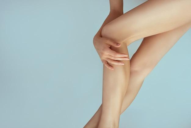Gładkie kobiece nogi po depilacji laserowej i dłoń na kolanie