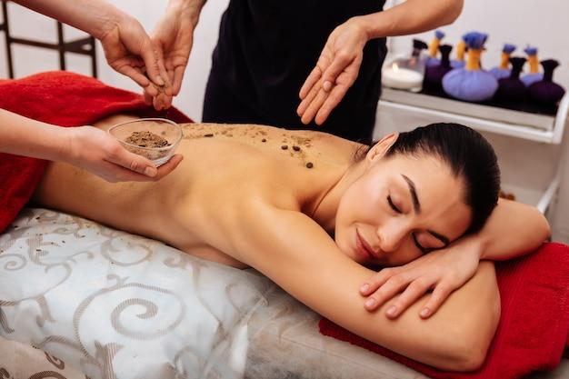 Gładsza skóra. przyjemna, ładna kobieta poddana zabiegowi pielęgnacyjnemu z ziarnami kawy podczas wizyty w centrum spa