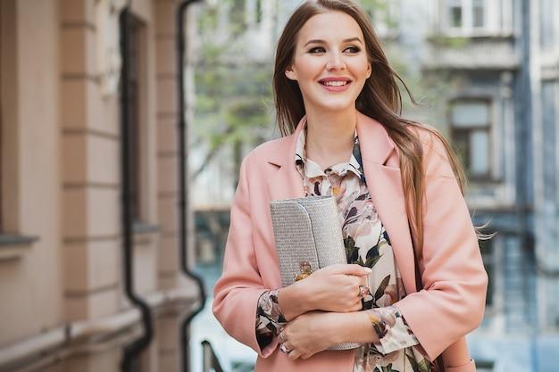 Glam atrakcyjna stylowa uśmiechnięta kobieta spaceru ulicą miasta w różowym płaszczu wiosenny trend w modzie trzymając torebkę