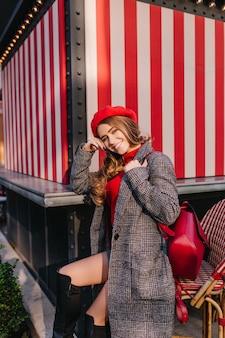 Glamorous dziewczyna w modnym tweedowym płaszczu siedzi na ulicy z ładnym uśmiechem