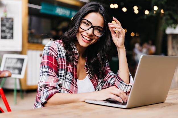 Glamorous kobieta freelancer ciesząc się rano i pracując z laptopem. zdjęcie wesołej pani łacińskiej w kraciastej koszuli pozuje w okularach.