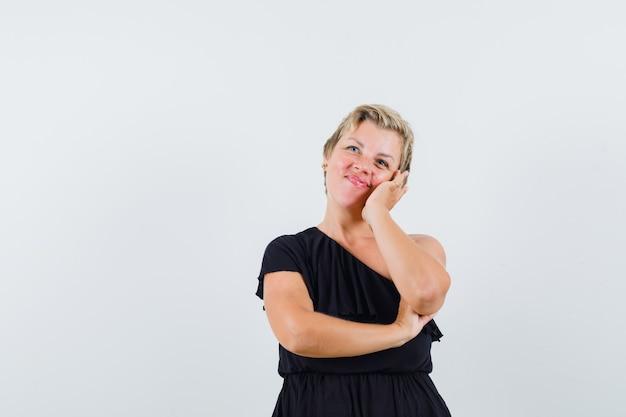 Glamorous kobieta pozuje trzymając dłoń na jej policzku w czarnej bluzce i patrząc jasno. przedni widok.
