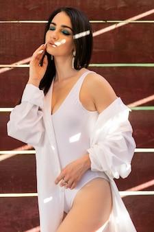 Glamorous młoda kobieta biała koszula pozowanie w pobliżu koncepcji ściany, mody i bielizny - piękny blond dama portret w białej koszuli, seksownym biustonoszu i majtkach. kobieta nosi bieliznę pozuje w jasnym świetle.