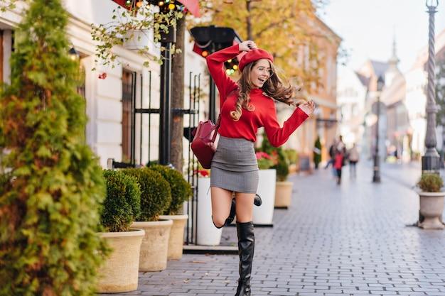 Glamorous młoda kobieta w wysokich do kolan butach stojących na jednej nodze na chodniku