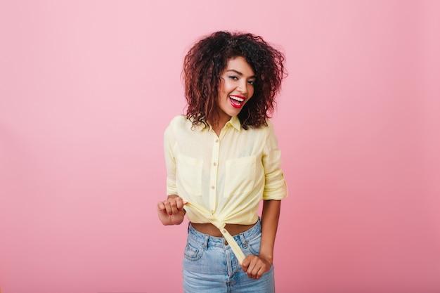 Glamorous szczupła młoda kobieta z afrykańską fryzurą pozuje z przyjemnością. stylowa łapanie dziewczyny w stroju vintage chłodzenie.