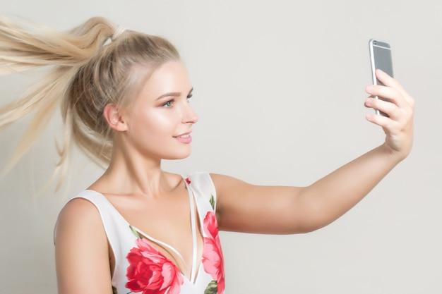 Glamour blond kobieta pwith włosy w ruchu, co selfie na telefonie komórkowym na szarym tle