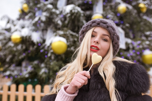 Glamour blond kobieta w szarym kapeluszu z dzianiny holing słodkich czekoladowych cukierków przed świątecznym świerkiem ze światłami