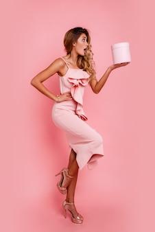 Glamour blondynka z niespodzianką na twarzy trzyma pudełko i stoi na ścianie róży w eleganckiej różowej sukience. ekstatyczne emocje.
