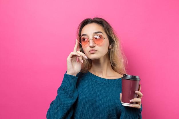 Glamour kobieta w okularach w niebieskim swetrze z napojem kawy na różowym tle