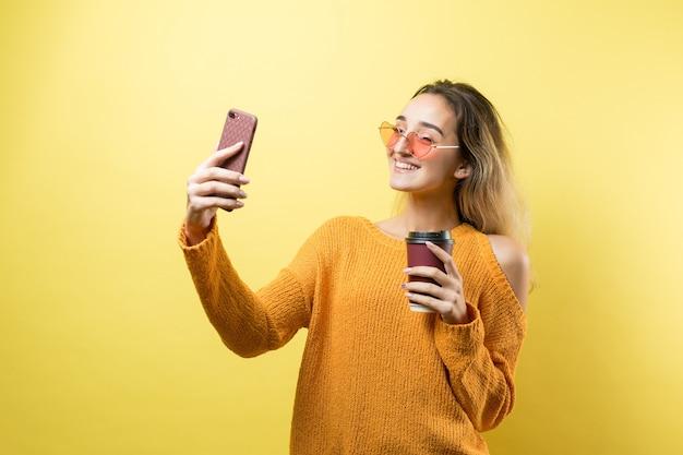 Glamour kobieta w okularach w pomarańczowym swetrze z napojem kawy na żółtym tle