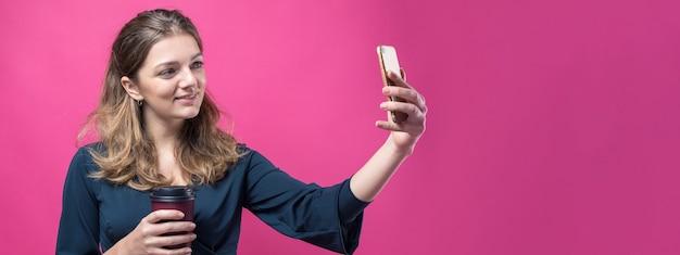 Glamour kobieta z napojem kawy na różowym tle