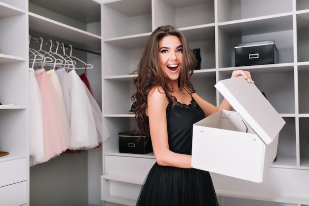 Glamour młoda kobieta, uśmiechnięta wesoła dziewczyna w ładnej szafie, chętnie znajduję, kupuję pudełko z butami, kupuje nowe obuwie. ma brązowe, długie kręcone włosy, ubrana jest w czarną sukienkę.