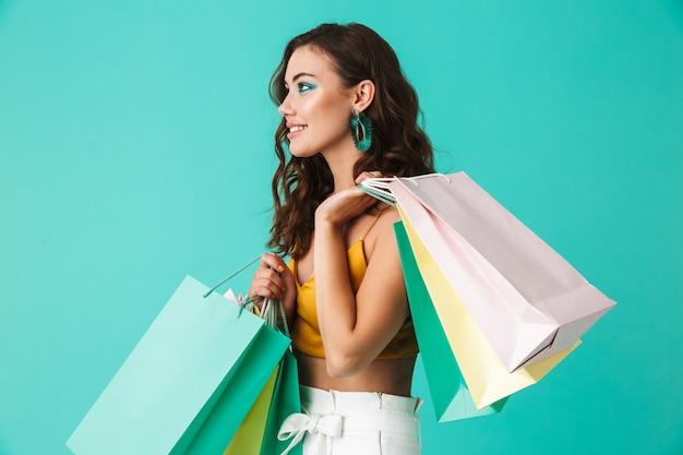 Glamour moda kobieta ubrana w stylowe kolczyki, niosąc kolorowe papierowe torby na zakupy z zakupami