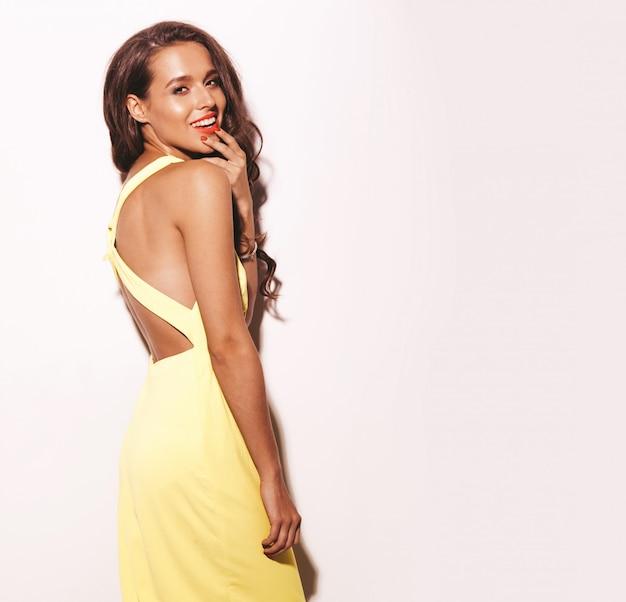 Glamour moda stylowy model piękna młoda kobieta z czerwonymi ustami w lecie jasny żółty strój na białym tle