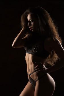 Glamour opalona brunetka kobieta z idealnym ciałem pozowanie w uwodzicielskiej bieliźnie. cień i światło