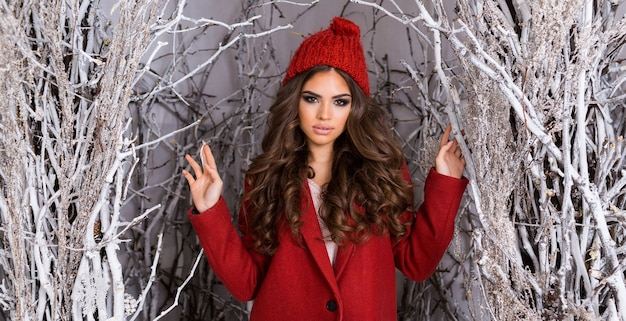 Glamour piękna kobieta w mroźnym winter park. piękna młoda kobieta w czerwonej czapce z dzianiny, faliste niesamowite fryzury, pełne usta i jasny makijaż.