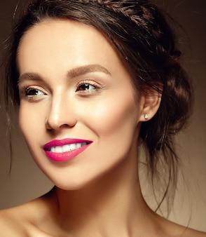 Glamour portret pięknej kobiety modelki z świeżego makijażu dziennego z czerwonymi ustami i czystą twarzą oraz romantycznej falistej fryzury na brązowej ścianie