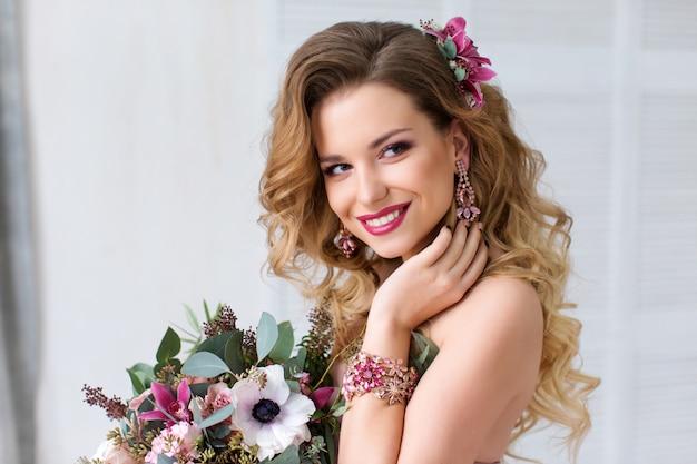 Glamour portret pięknej modelki z czerwonymi ustami i długimi blond włosami oraz stylowe kwiaty ślubne projektanta