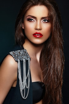 Glamour portret pięknej, seksownej stylowej brunetki młodej modelki rasy białej z jasnym makijażem, z czerwonymi ustami, z idealnie czystą skórą z biżuterią w czarnej tkaninie