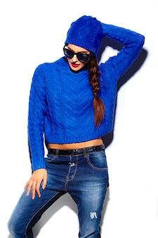 Glamour stylowy model piękna młoda kobieta z czerwonymi ustami w niebieskim swetrze hipster tkaniny w czapka