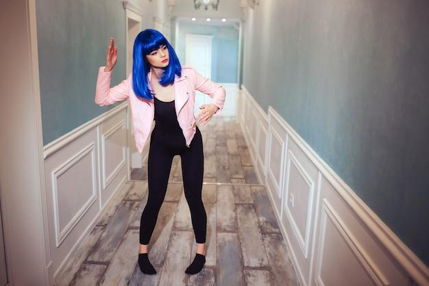 Glamour syntetyczna dziewczyna, sztuczna lalka o pustym wyglądzie i niebieskie włosy porusza się długim korytarzem.