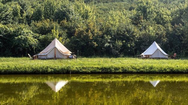 Glamping, kilka namiotów, jezioro na pierwszym planie, dookoła zgraja