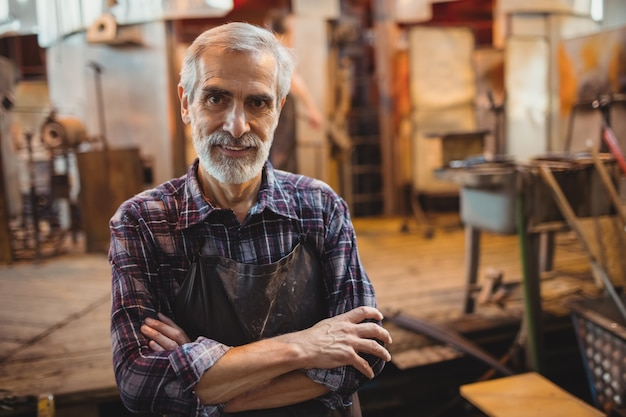 Glassblower stojący z rękami skrzyżowanymi w fabryce glassblowing