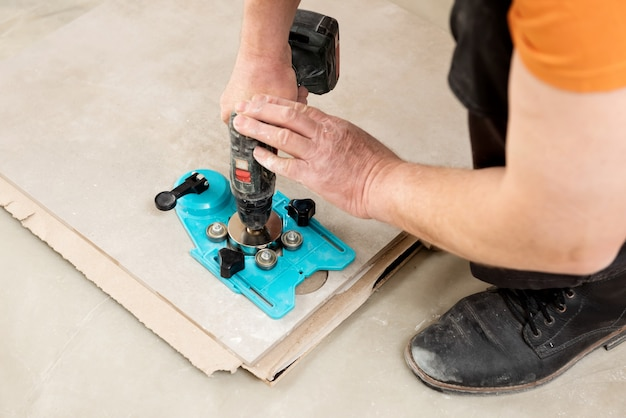 Glazurnik używa suwmiarki z przyssawką do wiercenia otworów w płytce ceramicznej z bliska