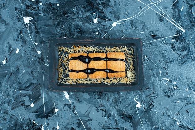 Glazurowana bułka tarta na drewnianym talerzu, na marmurowym tle.