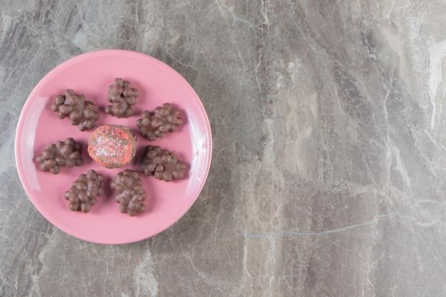 Glazurowane ciasteczka i czekoladki z orzechami laskowymi na talerzu na marmurze.