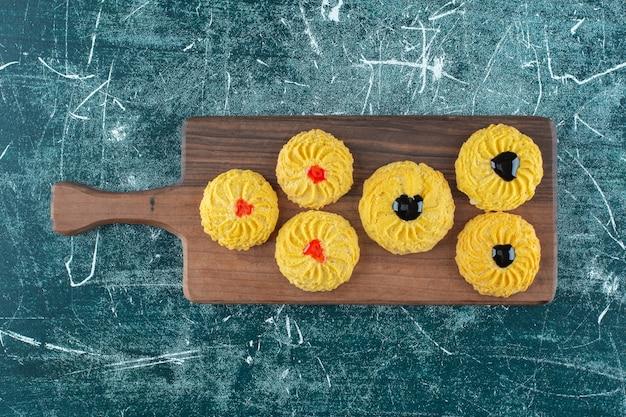 Glazurowane ciasteczka na desce do krojenia na niebieskiej powierzchni