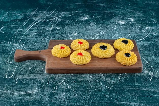 Glazurowane ciasteczka na desce do krojenia, na niebieskim tle. zdjęcie wysokiej jakości