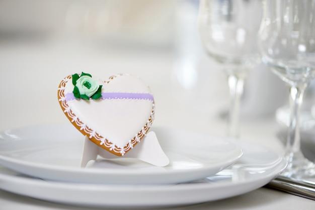 Glazurowane ciastko w kształcie serca - ozdobione zielonym glazurowanym kwiatkiem i drobnym wzorem stoi na białych talerzach jako dekoracja świątecznego stołu weselnego w pobliżu kieliszków