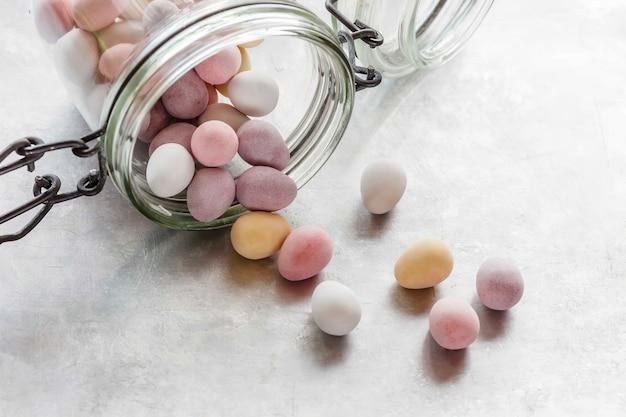 Glazurowane cukierki w szklanym słoiku i poza nim out