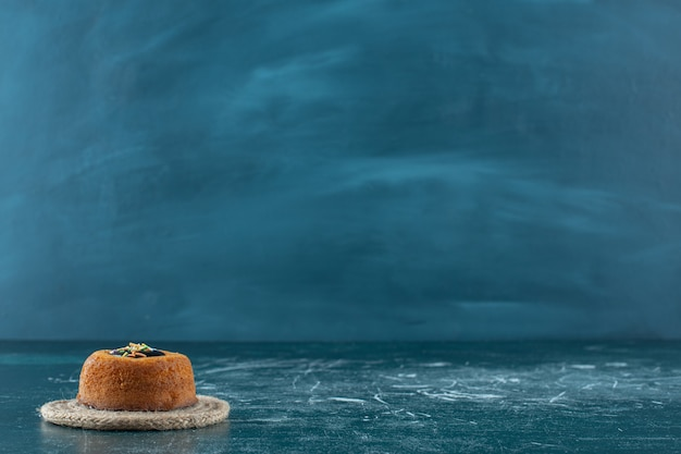 Glazurowany mini tort na podstawce, na niebieskiej powierzchni