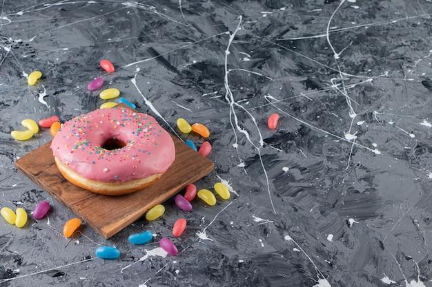 Glazurowany pączek na desce obok kolorowych cukierków, na mieszanym stole.