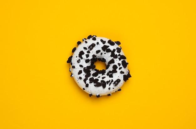 Glazurowany pączek posypany kawałkami czekolady na żółtym tle. ciasto ze słodyczy, niezdrowe jedzenie. widok z góry