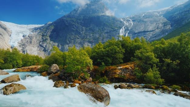Głazy górskiej rzeki duże górskie chmury lodowiec gęsta zielona roślinność