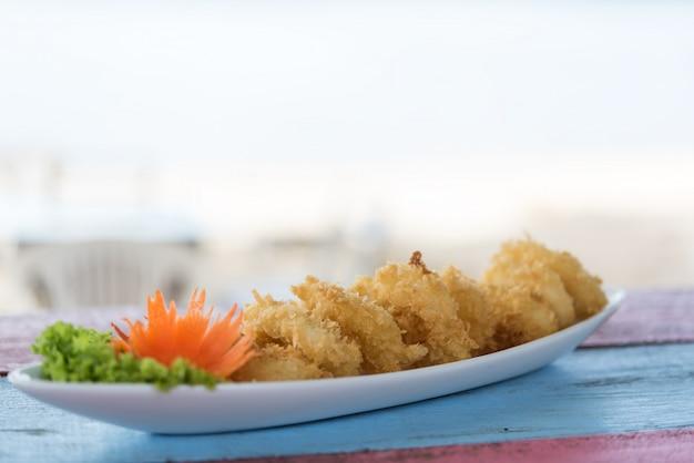Głęboka ciasto smażąca kałamarnica dzwoni calamari na rocznika drewna stole z zamazanym biel plaży tłem