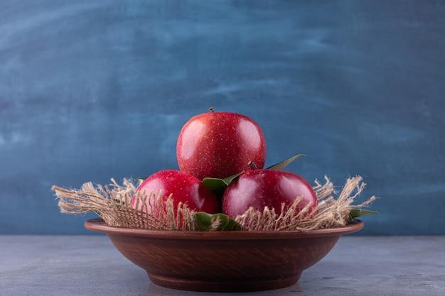 Głęboka miska z błyszczącymi czerwonymi jabłkami na kamieniu.
