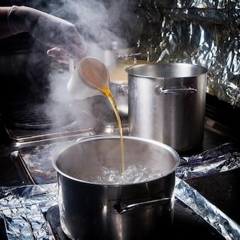 Głęboki garnek z widokiem z boku z wrzącą wodą, olejem i folią w piecu