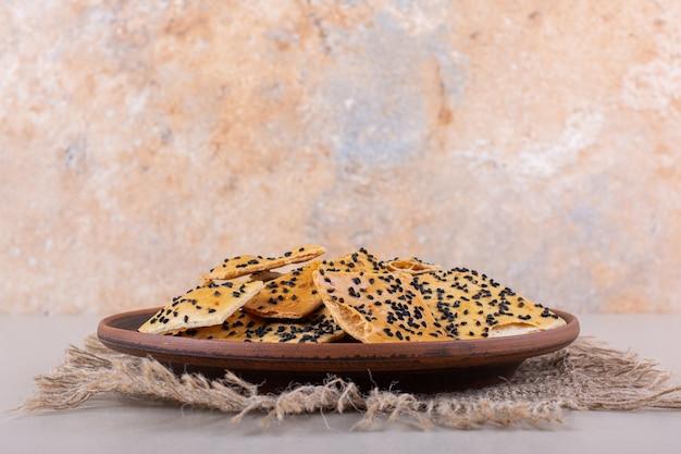 Głęboki talerz krakersów z czarnymi nasionami na białym tle. wysokiej jakości zdjęcie