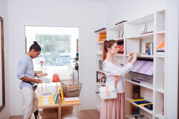 Głębokie czytanie. śliczna kobieta stojąca przy półkach z książkami, szukając prezentu