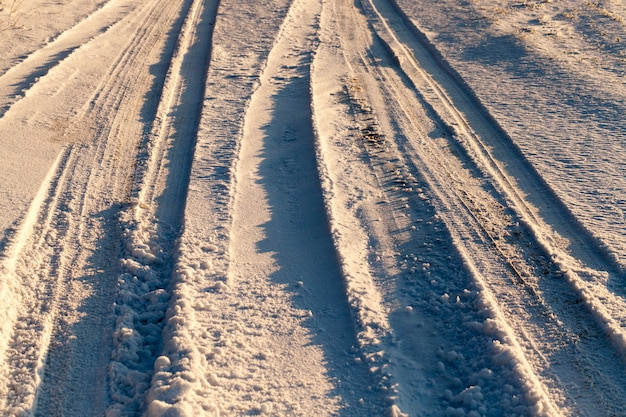 Głębokie i małe koleiny z kół samochodów na śniegu