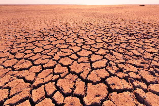 Głębokie pęknięcia w czerwonej ziemi jako symbol gorącego klimatu i suszy