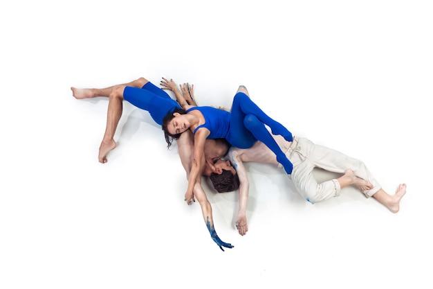 Głęboko. grupa tancerzy nowoczesnych, art contemp dance, niebiesko-białe połączenie emocji. elastyczność i gracja w ruchu i akcji na białym tle studia. moda i uroda, koncepcja grafiki.