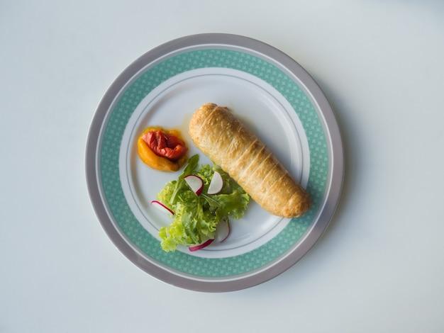 Głęboko smażona kiełbasa z grillowanymi warzywami na talerzu.