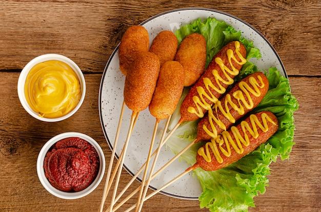 Głęboko smażone kukurydziane psy z musztardą i keczupem na drewnianym stole. koncepcja amerykańskiego fast foodów. widok z góry